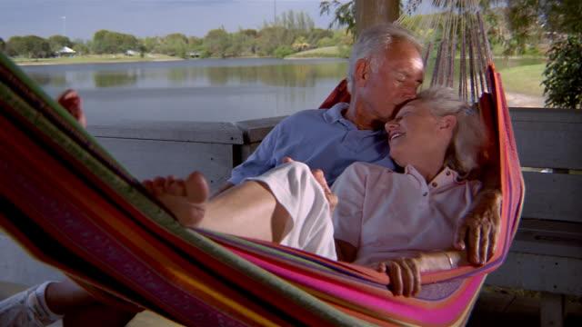 vídeos de stock e filmes b-roll de medium shot senior couple lying in hammock talking and laughing w/lake in background - cama de rede