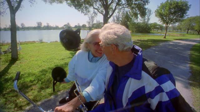 vídeos y material grabado en eventos de stock de medium shot senior couple on bicycles removing helmets and smiling at cam - medium group of animals