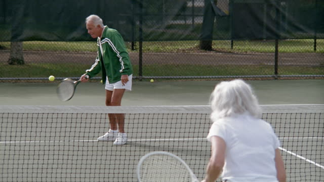 medium shot senior couple playing tennis - serving sport stock videos and b-roll footage
