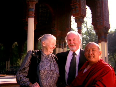 medium shot senior couple posing with asian male monk outdoors / mexico - 薄毛点の映像素材/bロール
