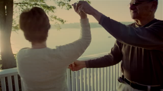 vidéos et rushes de medium shot senior couple slow dancing on deck - slow