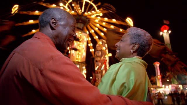 medium shot senior couple watching ride at amusement park at night - 遊園地点の映像素材/bロール