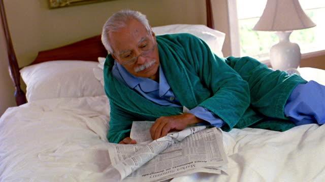 medium shot senior hispanic man lying on bed reading newspaper - ヘッドボード点の映像素材/bロール