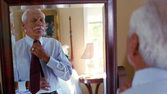 Medium shot senior Hispanic man tying tie in front of mirror
