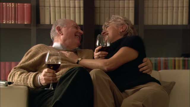 Medium shot senior man and mature woman holding glasses of red wine and sitting on sofa talking / snuggling