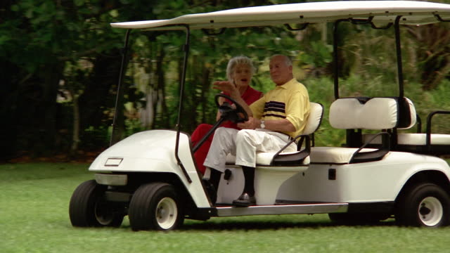 medium shot senior man and woman in golf cart smiling + bickering - golf cart stock videos & royalty-free footage