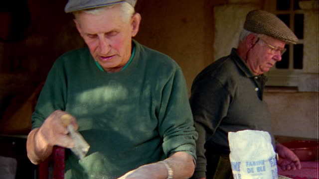 medium shot senior man cutting dough outdoors with other senior men in background / provence, france - french bakery stock videos & royalty-free footage