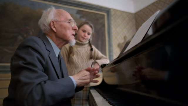 vídeos de stock e filmes b-roll de medium shot senior man giving piano lesson to young girl (man playing and writing on sheet music) - piano