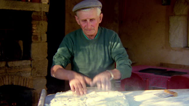 Medium shot senior man in hat kneading dough outdoors / Provence, France
