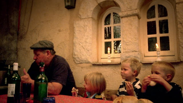 Medium shot senior man sitting at table with three young children eating bread / Provence, France