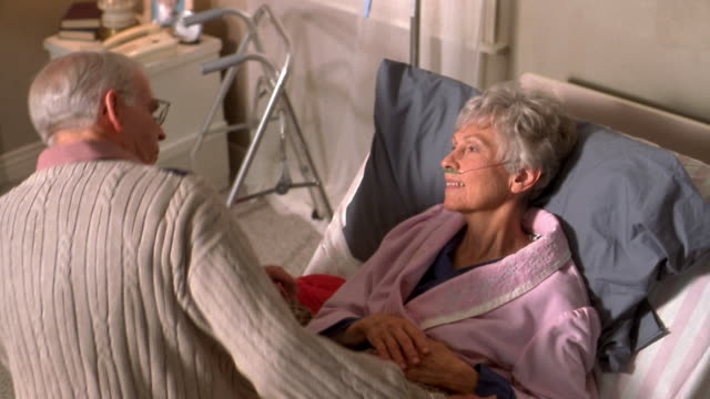 Medium shot senior man sitting on bed by sick elderly wife and comforting her w/walker by bedside