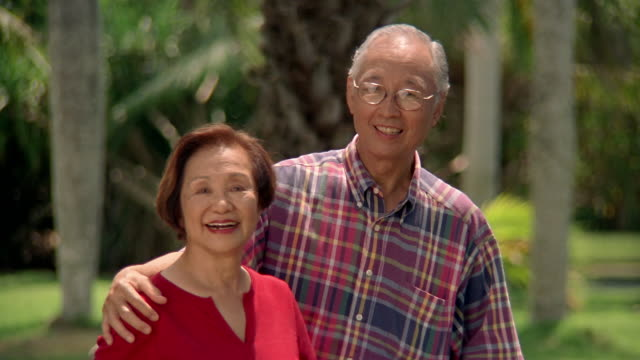medium shot senior man with his arm around senior woman / smiling at cam and each other - other stock videos & royalty-free footage