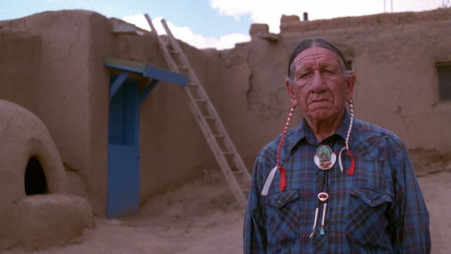 medium shot senior native american man posing in front of adobe dwelling / taos, new mexico - north american tribal culture stock videos & royalty-free footage
