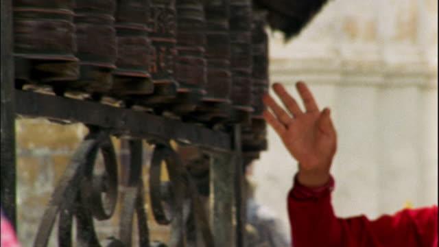 Medium shot senior person spinning prayer wheels at Swayambhunath Temple / Kathmandu, Nepal