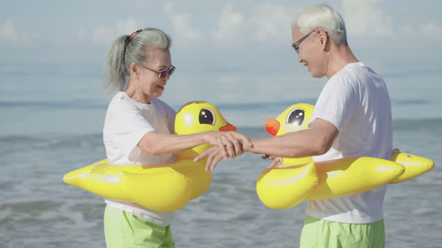 medium shot: senior wife playing seawater feeling happiness, smiling, with her senior husband, having a summer vacation together, a mature couple in a couple of cloth, a white t-shirt, green shorts at the beach with a yellow swimming ring. - swimming shorts stock videos & royalty-free footage