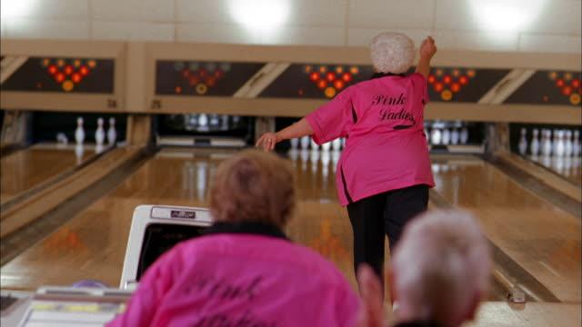 Medium shot senior woman bowling and getting gutter ball / smiling w/teammates