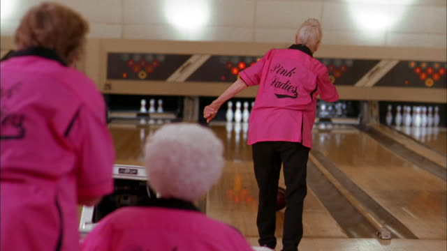 Medium shot senior woman bowling and missing pins / turning + smiling w/teammates