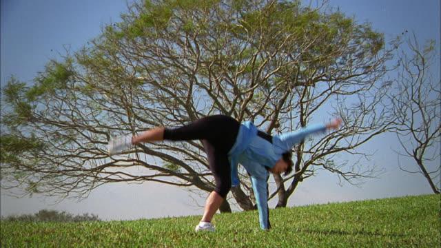 medium shot senior woman doing cartwheel outdoors - cartwheel stock videos & royalty-free footage