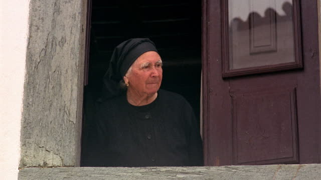medium shot senior woman in black looking out window / monsaraz, portugal - portuguese culture stock videos & royalty-free footage