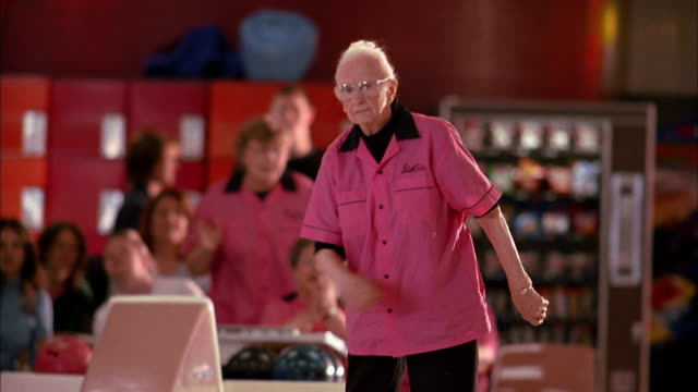 medium shot senior woman in 'pink ladies' jersey bowling and dancing - ボウリング点の映像素材/bロール