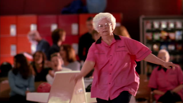 medium shot senior woman in 'pink ladies' team jersey bowling and cheering w/teammates - young at heart stock videos & royalty-free footage