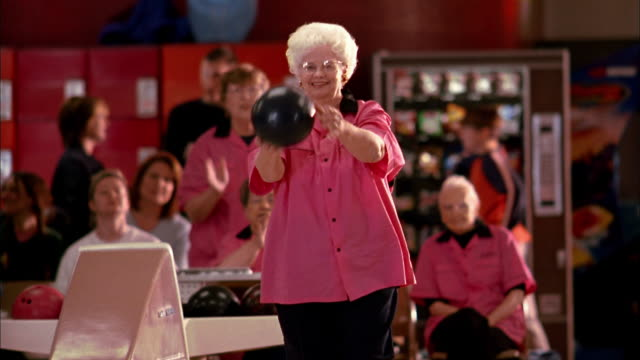 Medium shot senior woman in 'Pink Ladies' team jersey bowling and cheering w/teammates