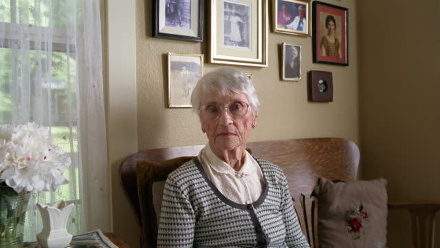medium shot senior woman sitting in living room next to wall of old photographs / des moines, king county, washington, usa - halbnahe einstellung stock-videos und b-roll-filmmaterial