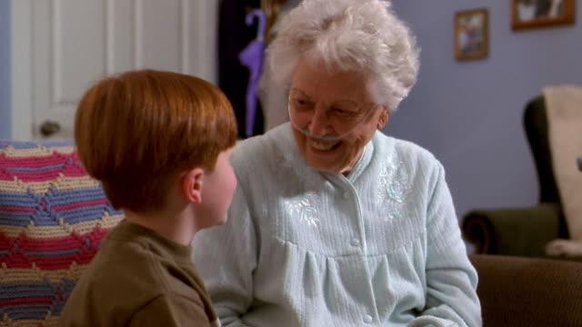 medium shot senior woman wearing iv tube in nose talking to grandson on sofa - nightdress stock videos & royalty-free footage