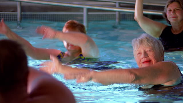 Medium shot seniors in swimming pool doing exercises with instructor in foreground