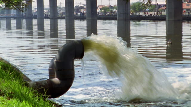 medium shot sewer pipe spraying water into river / jakarta - sewage treatment plant stock videos & royalty-free footage