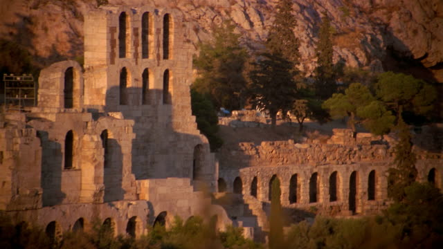 Medium shot shadows on Odeum (Theater) of Herodes Atticus / zoom out view of Acropolis / Athens, Greece