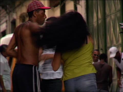 2003 medium shot shirtless man smoking a cigarette and dancing with two women on street / cuba - 男性と複数の女性点の映像素材/bロール