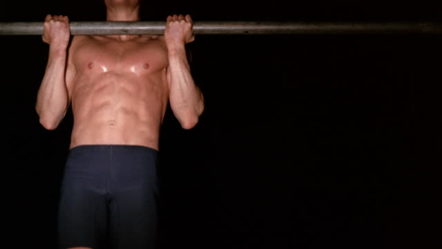Medium shot shirtless muscular man doing chin ups on bar