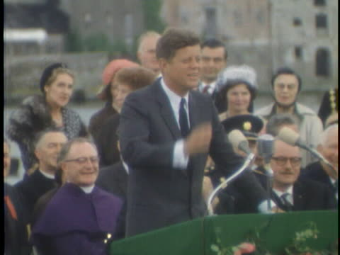 medium shot shot of president john f. kennedy standing at a green lectern with microphones atop it. there is a crowd of people sitting behind him as... - john f. kennedy us president stock videos & royalty-free footage