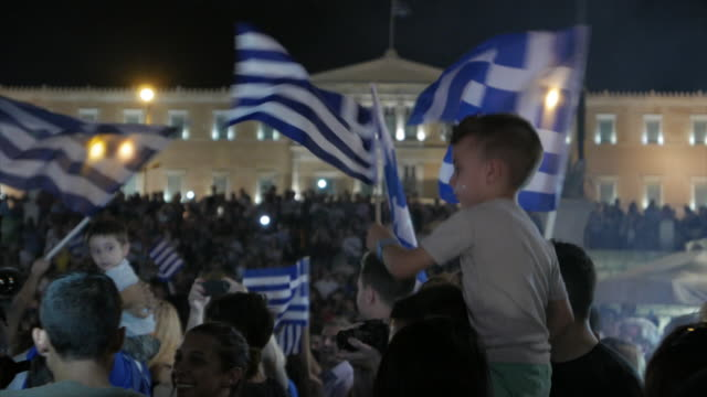 medium shot showing a child waving the greek flag in front of the greek parliament building on the night that the referendum results over bailout... - ユーロ圏債務危機点の映像素材/bロール