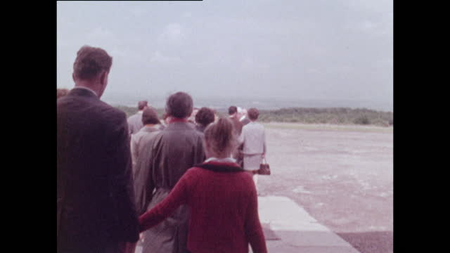medium shot showing a group of tourists walking into buchenwald concentration camp; 1970. a young girl takes the hand of a man. - horizon over land stock videos & royalty-free footage