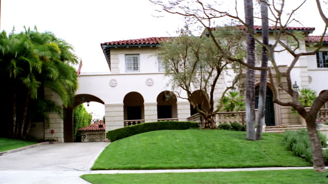 Medium shot side car point of view driving past large Spanish-style house / Beverly Hills, California