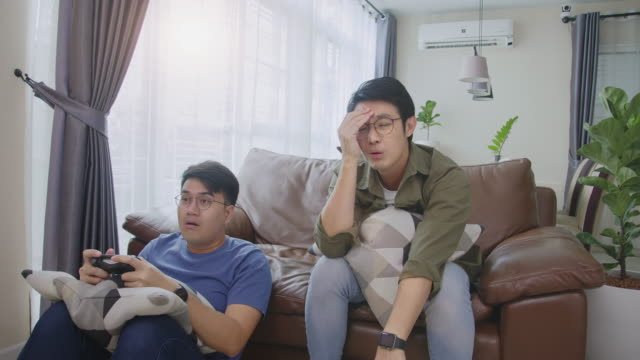medium shot side view 4k resolution attractive two adult asian men friends holding joystick or game controller and playing video games console together at home. two men reaction loss on the game play. - computer game control stock videos & royalty-free footage