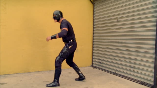"""medium shot side view luchador """"shadow"""" flexing muscles in front of garage door/ monterrey, mexico - elbow pad stock videos & royalty-free footage"""
