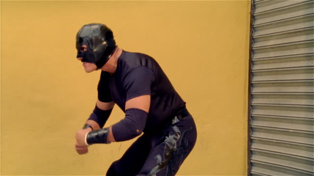 """medium shot side view luchador """"shadow"""" in wrestling stance/ monterrey, mexico - elbow pad stock videos & royalty-free footage"""