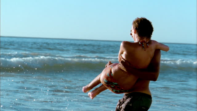 vídeos de stock e filmes b-roll de medium shot side view man laughing and running / carrying woman in surf - tronco nu