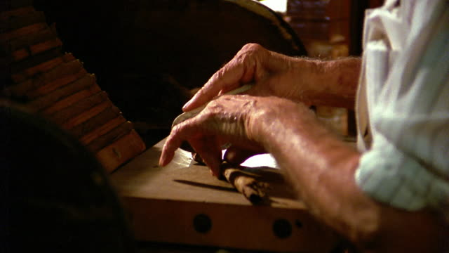 medium shot side view man's hands rolling and cutting cigar on wooden surface / tampa, florida - cigar stock videos & royalty-free footage