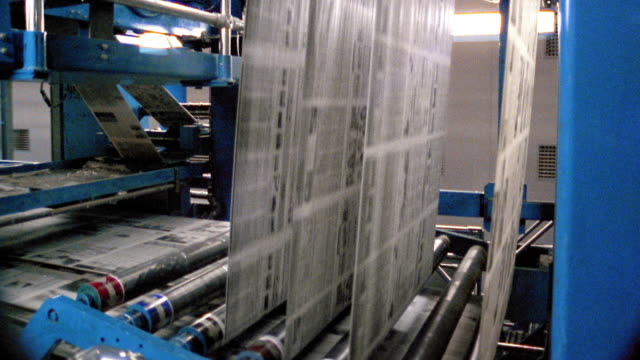 medium shot side view newspapers running through printing press / los angeles, california - druckmaschine stock-videos und b-roll-filmmaterial