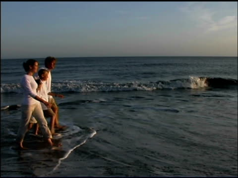 medium shot side view of a family holding hands walking together in the ocean surf at sunset. - see other clips from this shoot 1135 stock videos & royalty-free footage