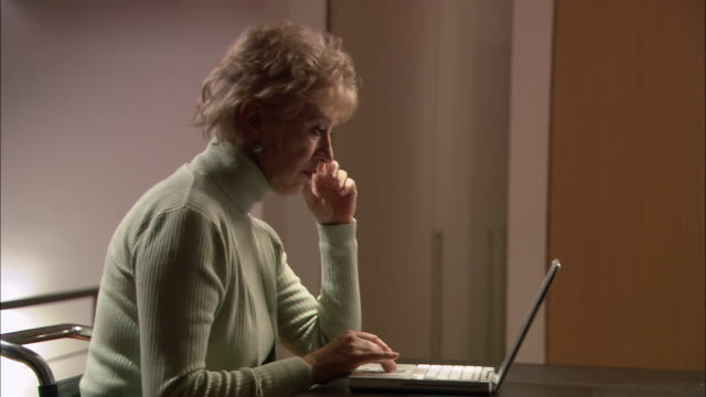 medium shot side view of mature woman sitting at table using laptop computer / calling man into room to look at screen - turtleneck stock videos & royalty-free footage