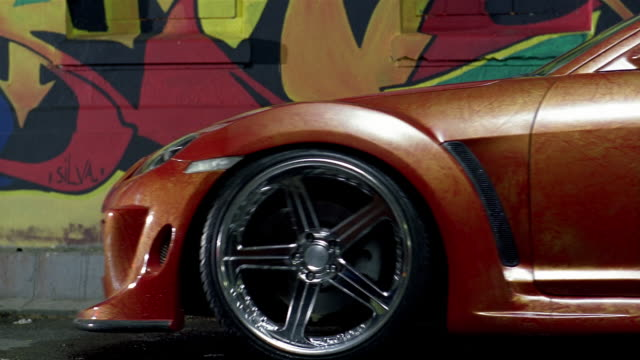 medium shot side view of red race car with chrome rims pulling up in front of grafitti mural / jakarta - wheel stock videos and b-roll footage