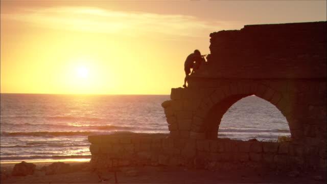 medium shot silhouette- man and woman climb caesaria ruins / caesaria israel - israele video stock e b–roll