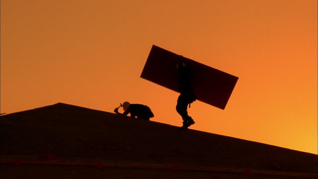 Medium shot silhouette of construction worker carrying wood panel on roof /  Phoenix, Arizona
