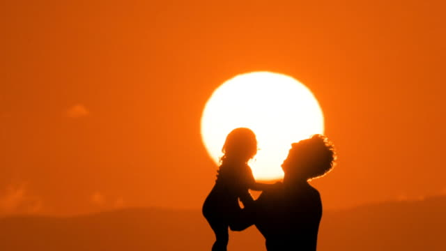stockvideo's en b-roll-footage met medium shot silhouette of man lifting, holding, tossing and turning child in air with sun in background / maui, hawaii - oppakken