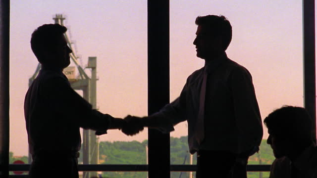medium shot silhouette of two businessmen shaking hands and slapping a high five with others clapping / portugal - high five stock videos & royalty-free footage